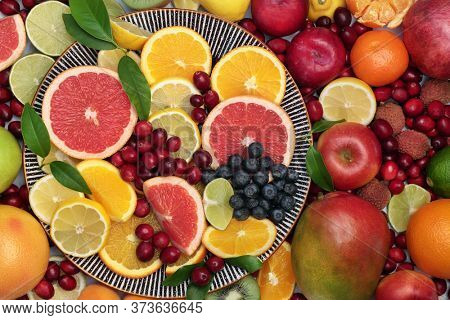 Large healthy fresh fruit collection on a round plate and loose. Super food very high in antioxidants, vitamins, dietary fibre and anthocaynins. Top view.