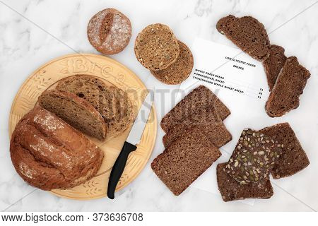 Low glycemic bread selection for diabetics with corresponding list, with breads high in antioxidants, smart carbs & omega 3 fatty acids. Below 55 on the GI index. Top view on marble.
