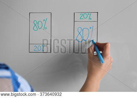 Woman Writing 80/20 Rule Representation On Flip Chart Board, Closeup. Pareto Principle Concept