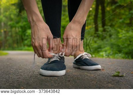 Close-up Of Women\'s Hands Tying Shoelaces In Dark Blue Sneakers On A Jog In The Woods.