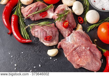 Several Pieces Of Raw Meat With Garlic, Rosemary, Mushrooms, Tomatoes And Red Chili Pepper On A Blac
