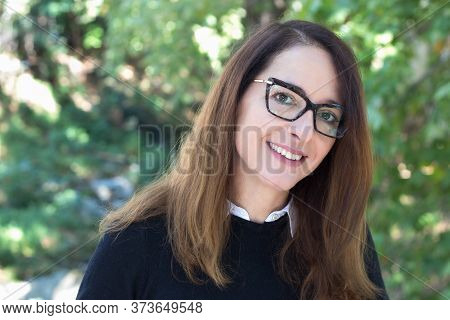 Portrait Of A Mature Woman, 46 Years, Looking At Camera, Outdoors, Wearing Glasses, Cat Style.