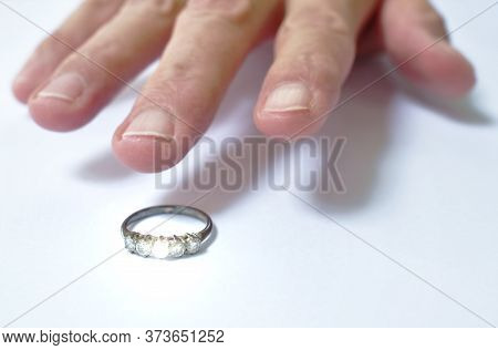 Man Hand Grabbing Diamond Wedding Ring On White Background