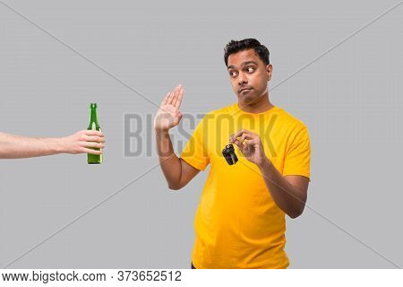 Indian Man Saying No To Beer Bottle Holding Car Keys. Dont Drink And Drive Concept. Man Doesnt Drink