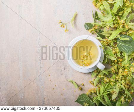 Cup Of Herbal Linden Tea With Linden Flowers. Tea From Linden. Fresh Flowering Linden On A Wooden Ba