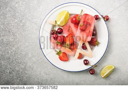 Berry Popsicle With Wooden Sticks On Concrete Counter. Homemade Strawberry Frozen Fruit Bars. Strawb
