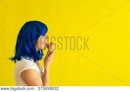 A Beautiful Woman With Blue Hair Stands In Profile And Licks A Horn Of Raspberry Ice Cream On A Yell