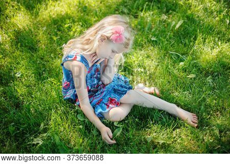 Sad Young Girl Sitting On Ground Outdoor On Summer Sunny Day. Pensive Little Child Dreaming Thinking