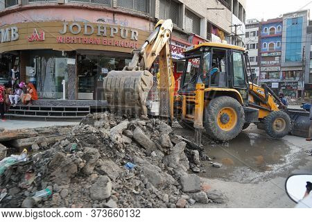Jcb Earth Moving Machine Working On A Road. Jcb Bucket Loader Is Repairing A Section Of A Dirt Road.