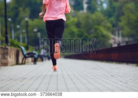 Sports Woman Is Running In The Park. Back View Of Girl In Sportswear Running Along Riverside.