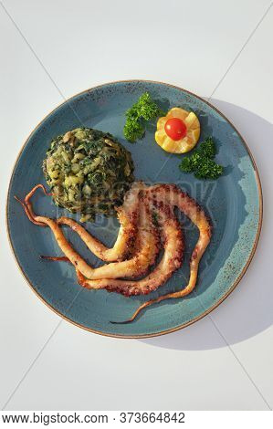 Balkan Cuisine. Plate With Grilled Octopus And Green Leafy Vegetables On White Table. Flat Lay, Copy