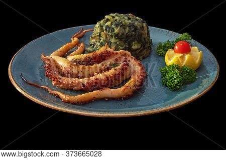 Balkan Cuisine. Plate With Grilled Octopus And Green Leafy Vegetables, Isolated On Black Background