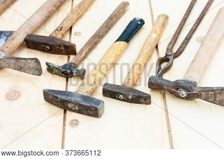 Set Of Vintage Well Used Hand Construction Tools For Handyman, Hammers, On A Wooden Background .