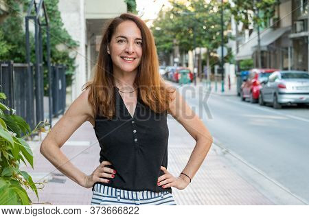 Portrait Of A Mature Woman, 40s, Smiling Looking Camera With Her Hands On Her Hips Outdoors In A Cit