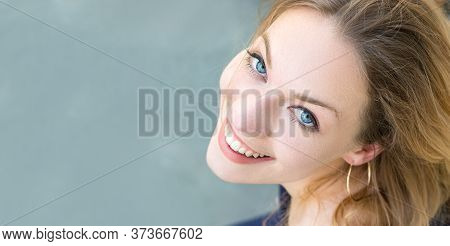 Portrait Of An Austrian Young Woman Blonde With Blue Eyes Looking Up, Toothy Smile, Healthy Teeth.