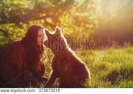 Woman And Dog On The Meadow At Sunset.
