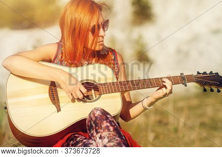 Woman Playing With Guitar And Blurred Background. Old Photo Effect.