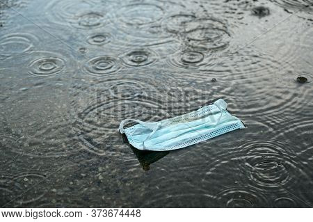 Surgical Face Mask Against Coronavirus Infection Discarded On The Black Asphalt In The Rain At The E