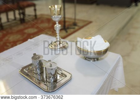Catholic Liturgical Objects Ready On Table At Church. Chalice, Communion Wafers, Wine And Water Jugs