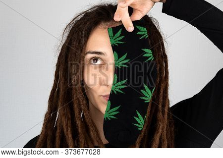 Funny Girl With Dreadlocks Holds Sock With Cannabis Print On Her Face