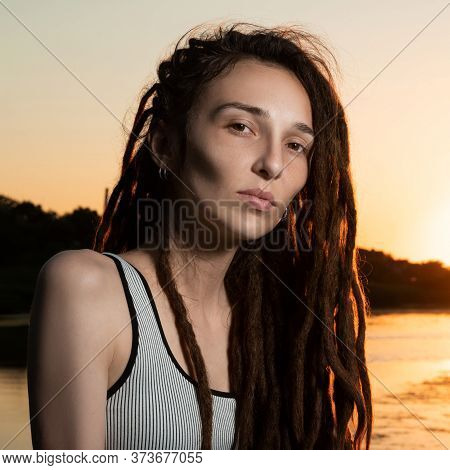 Beautiful Girl With Dreadlocks Without Makeup On The River In The Setting Sun