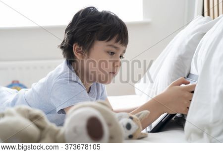 6-7 Year Old Boy Playing With Dog Toy And Watching Cartoon On Tablet,happy Child Lying In Bed Playin