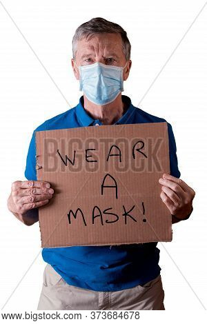 Senior Caucasian Man Holding A Blank Cardboard Sign Saying Wear A Mask. He Is Isolated Against A Whi