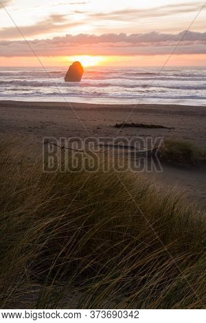 Tranquil Afternoon In Gold Beach With The Sunsetting Behind A Thick Fog Bank And Grassy Dunes In The