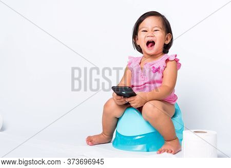 Asian Little Cute Baby Child Girl Education Training To Sitting On Blue Chamber Pot Or Potty And Pla