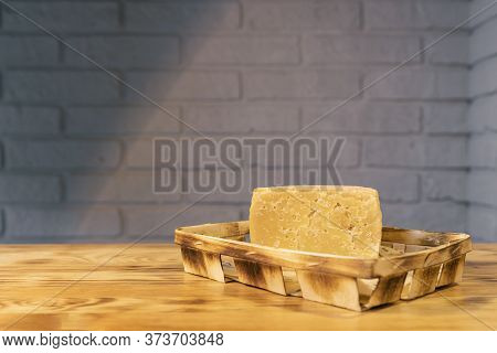 A Piece Of Aged Cheese On A Wooden Table Against A Brick Wall.