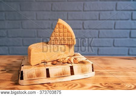 Aged Cheese And Nuts On A Wooden Table