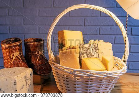 A White Basket Filled With Various Cheeses Against A Brick Wall.