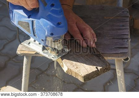 A Man Processes Wood With An Electric Jigsaw. A Carpenter Sawing A Board With A Blue Electric Jigsaw