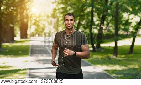 Happy Jogger With Mobile Phone Listening To Music And Enjoying His Run At Park On Sunny Morning. Pan