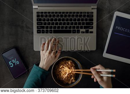 Woman Eating Noodle While Working On Computer Laptop, Mobile Phone And Tablet. Top View. Unhealthy F