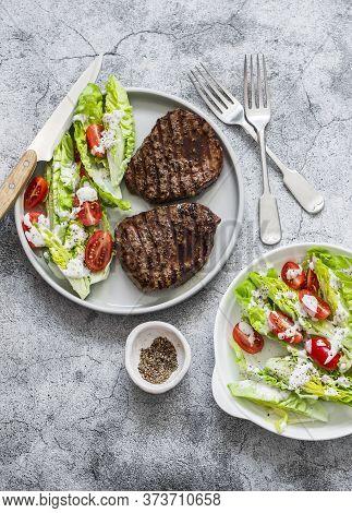 Grilled Beef  Steak And Fresh Romaine Salad Cherry Tomatoes Yogurt Dressing Salad On A Grey Backgrou