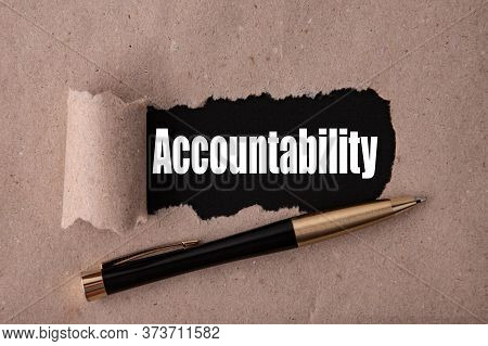 The Word Accountability Is Written Under Tear Paper On A Black Background With A Pen
