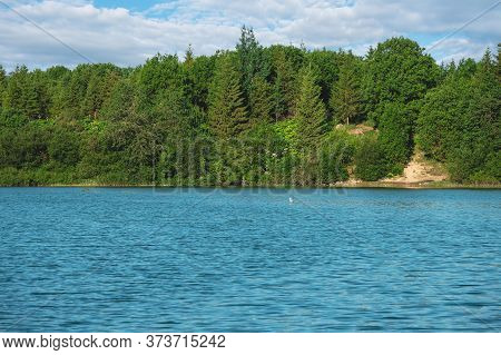 Tranquil View To Bright Forest Near Steep Shore Of Mountain Lake. Coniferous Trees On Steep Slope.