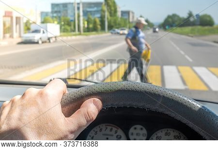 View From The Car, The Man Hand On The Steering Wheel Of The Car, Located Opposite The Pedestrian Cr