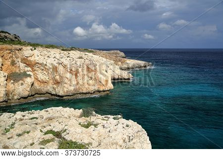 Landscape With Rocky Coastline And Sea, Horizon, Swirling Clouds In The Sky, Relaxing Quiet Area Wit