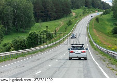 Car Universal Rides On An Asphalt Road In The Background Forest Landscape And Car Traffic. The Conce
