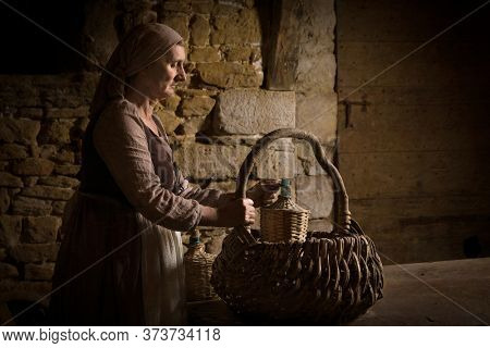Woman in medieval peasant dress checking her food basket in the cellars of a property released authentic medieval castle in France