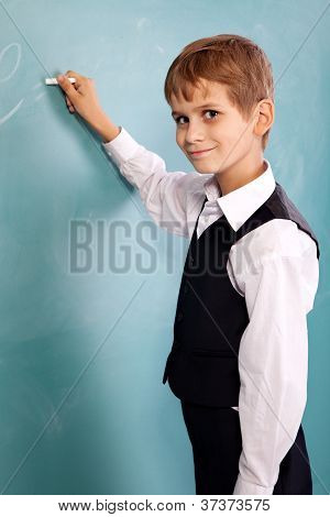 School Student Writing On Blackboard At School