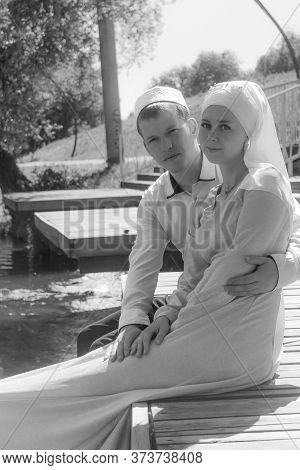 Couple Young Muslim Man And Woman Sittin On Wooden Stairs Near The Lake. Muslim Tatar Wedding. Black
