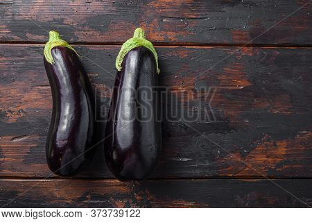 Fresh Healthy Raw Purple Aubergine On A Kitchen Old Dark Wooden Table. Top View, Space For Text.