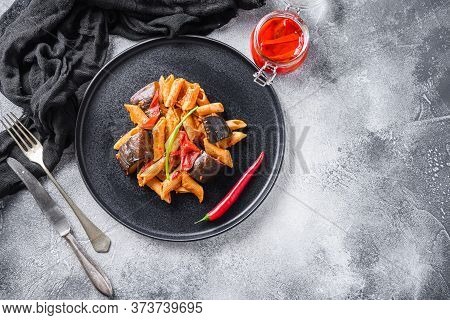 Aubergine Penne Eggplant Pasta, Pepper Tomatoe Sauce, On Black Plate Overgrey Concrete Background  S