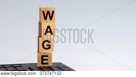 Text Of Wage On Wooden Cubes. The Cubes Are Located On The Keyboard.
