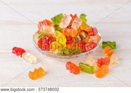 Multicolored Gummy Bears Candy On A Glass Plate Over White Wood Table. Jelly Sweets Of Differenr Col