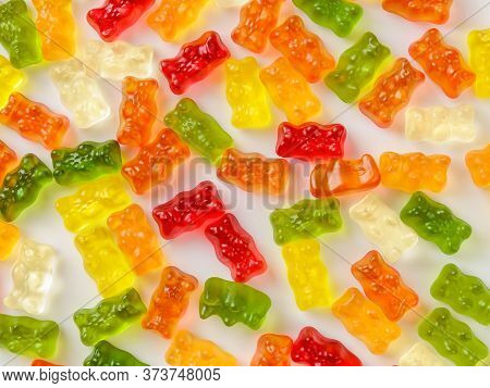 Background Of Multicolored Gummy Bears Candy On White Surface. Jelly Sweets Of Differenr Colors. Pop