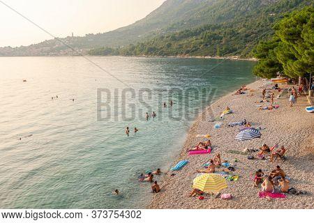 Makarska, Croatia - September 2, 2019: Beautiful beach at Adriatic Sea in Makarska Riviera at sunset, Dalmatia, Croatia